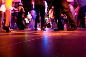 A low shot of the dance floor with a crowd dancing at an event under the colorful lights